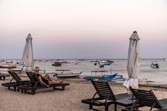 坐在萨努尔海滩日落的巴厘岛印度尼西亚女孩 免版税库存照片
