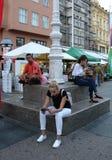 坐在萨格勒布街道的三青年人  免版税图库摄影
