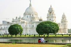 坐在著名维多利亚纪念品前面的两青年人  免版税库存图片