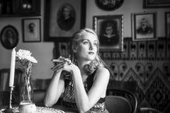 坐在葡萄酒咖啡馆的一个年轻减速火箭的夫人的画象 图库摄影