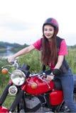 坐在葡萄酒摩托车的轮子的女孩户外 免版税库存图片