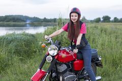 坐在葡萄酒摩托车的轮子的女孩户外 库存图片
