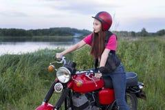 坐在葡萄酒摩托车的轮子的女孩户外 免版税库存照片