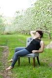 坐在葡萄酒椅子的妇女 免版税库存照片