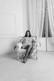 坐在葡萄酒椅子的衬衣的美丽的女孩 免版税图库摄影