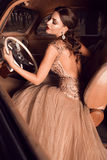 坐在葡萄酒汽车后轮子的美丽的女孩  库存照片
