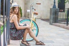 坐在葡萄酒自行车附近的女孩在公园 免版税库存照片