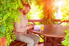 坐在葡萄酒设计木树荫处的有胡子的人 库存照片