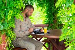 坐在葡萄酒设计木树荫处的有胡子的人 图库摄影