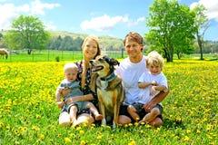 坐在蒲公英领域的愉快的家庭 免版税库存照片