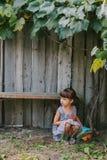 坐在藤下的国家女孩 女孩她使用的玩具 库存照片
