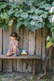 坐在藤下的国家女孩 女孩她使用的玩具 免版税库存照片