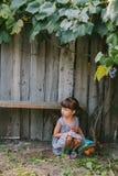 坐在藤下的国家女孩 女孩她使用的玩具 免版税库存图片