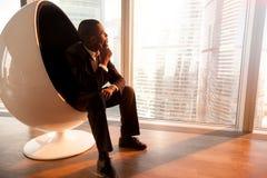 坐在蛋椅子的非裔美国人的商人享受sunse 免版税库存照片