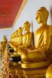 坐在行的金黄Buddhas 图库摄影