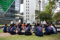 坐在街市新加坡的男孩和女孩 免版税库存照片