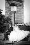 坐在街灯bw旁边的新婚佳偶 免版税库存图片
