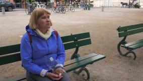 坐在街道上的一条长凳和吃从包裹的妇女甜点 股票视频