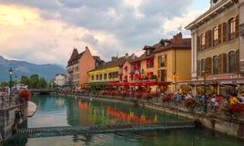 坐在街道咖啡馆和走沿Le Thiou河的人们在阿讷西法国晚上 库存图片