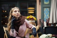 坐在街道咖啡馆的美丽的时髦的少妇画象  在旁边查找设计 背景秀丽城市生活方式都市妇女年轻人 女性方式 库存照片
