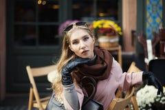 坐在街道咖啡馆的美丽的时髦的少妇画象  式样看的照相机 关闭 背景秀丽城市生活方式都市妇女年轻人 免版税库存图片