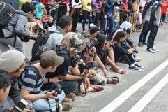 坐在街道的一个小组摄影师 免版税库存图片