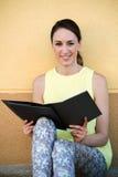 坐在街道的可爱的少妇读小册子 免版税库存图片