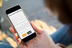 坐在街道的妇女举行她的智能手机读书期限 免版税图库摄影