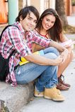 坐在街道的年轻学生拿着书。 库存图片