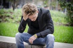 坐在街道边的沮丧的年轻白人 免版税图库摄影