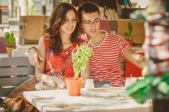 坐在街道露天咖啡馆的年轻美好的愉快的爱恋的夫妇,拥抱 爱情小说起点  关系爱 免版税库存照片