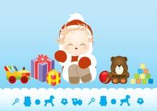 坐在衣服圣诞老人的新出生的婴孩围拢由玩具和礼物 免版税库存图片
