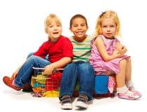 坐在衣服提袋的三个孩子 免版税库存照片