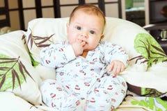 坐在衣服的美丽的新出生的男孩 图库摄影