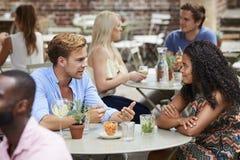 坐在表上的夫妇在一起享受饮料的客栈庭院里 免版税库存图片