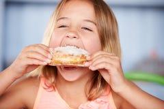 坐在表上的女孩吃含糖的多福饼 免版税库存照片