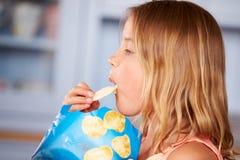 坐在表上的女孩吃土豆片 免版税库存照片