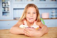 坐在表上的女孩看含糖的蛋糕板材  库存图片