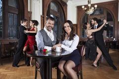 坐在表上的微笑的夫妇,当执行探戈时的舞蹈家 免版税图库摄影
