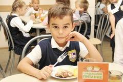 坐在表上的快活的男小学生在吃膳食的学校食堂 饮用的汁液-俄罗斯,莫斯科,第一所高中,冷杉 免版税库存照片