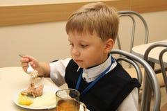 坐在表上的快活的男小学生在吃膳食的学校食堂 饮用的汁液-俄罗斯,莫斯科,第一所高中,冷杉 免版税图库摄影