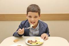 坐在表上的快活的男小学生在吃膳食的学校食堂 饮用的汁液-俄罗斯,莫斯科,第一所高中,冷杉 免版税库存图片