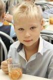 坐在表上的快活的男小学生在吃膳食的学校食堂 饮用的汁液-俄罗斯,莫斯科,第一所高中,冷杉 库存图片