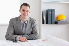 坐在表之后的微笑的建筑师 免版税库存照片