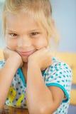 坐在表的小女孩 免版税库存照片