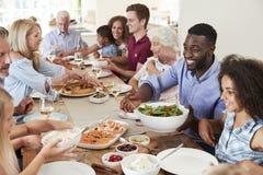 坐在表附近和享受膳食的小组多代的家庭和朋友 免版税库存照片