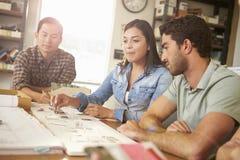 坐在表附近的三位建筑师开会议 免版税库存照片