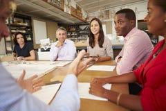 坐在表附近的六位建筑师开会议 免版税库存照片