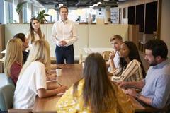 坐在表附近的商人和女实业家地址组年轻候选人 库存照片