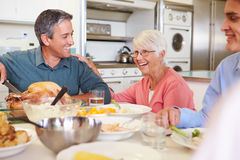 坐在表附近的多代的家庭吃膳食 免版税库存图片